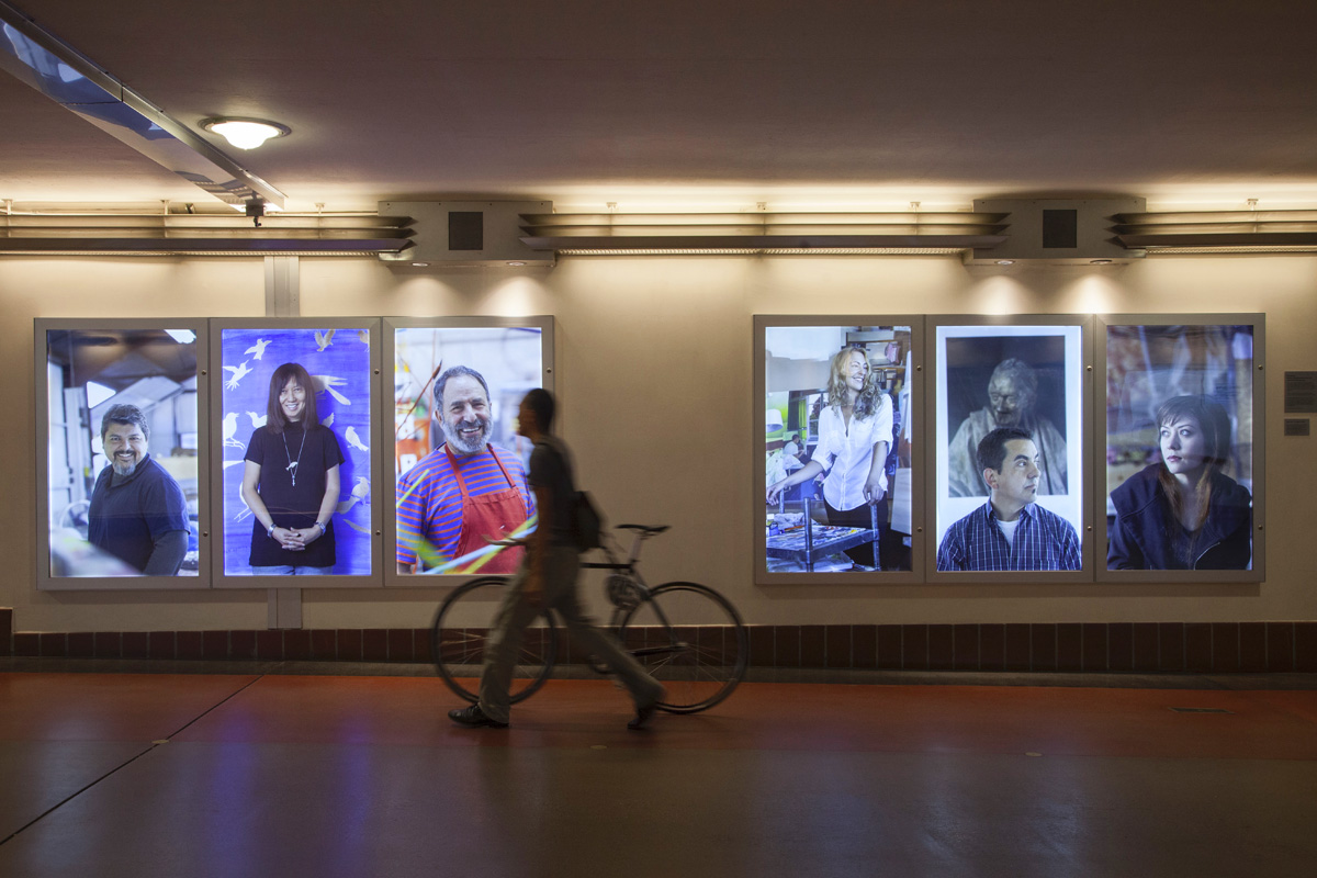 Person with bike passing Installation of portraits of Metro Artists